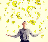 Businessman trying to catch falling euros. — Stock Photo