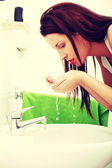 Young woman washing face in the bathroom. — Stockfoto