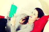 Beautiful woman reading a book on a sofa. — Stock Photo
