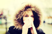 Young woman sneezes during cold day. — Stock Photo
