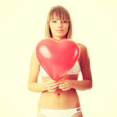 Woman in bikini with heart shaped baloon — Stock Photo