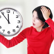 Shocked woman holding clock — Stock Photo