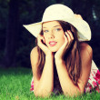 Girl in hat lying on the grass — Stock Photo #42258623