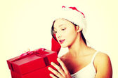 Teen girl holding and looking at gift. — Stockfoto