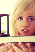 Teenager with book and hourglass — Stockfoto