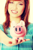 Woman showing her pink piggy bank — Stock Photo