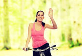Attractive brunette woman with bike — Stock Photo