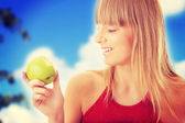 Young blond woman with green apple — Foto de Stock
