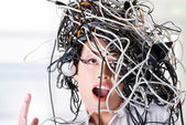 Troubled businesswoman with cables on head — Stock Photo