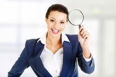 Business woman looking into a magniying glass — Stock Photo