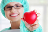 Smiling female doctor or nurse holding heart — Stock Photo