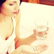 Woman holding pills and a glass of water. — Stock Photo #42743509