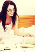 Pleased femal studying in bed. — Stock Photo
