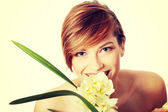 Beautiful young woman with orchid flower — Stock Photo