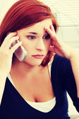 Upset woman talking by phone — Stockfoto