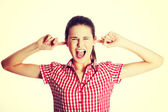 Upset female teen clogging her ears. — Stock Photo