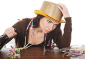 Young drunk woman by a table and with empty bottle. — Stock Photo
