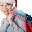 Woman in santa hat with shopping bags. — Stock Photo
