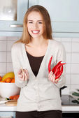 Woman is holding chili peppers and garlic. — Stock Photo