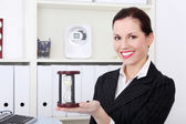 Business woman holding hourglass. — Stock Photo