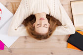 Relaxed young student woman lying on the floor — Stock Photo