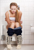 Woman is sitting on the toilet. — Stock Photo
