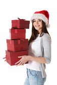 Woman in santa hat, holding stock of presents. — Stock Photo
