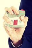 House model being squeezed in woman's hand. — Stock Photo