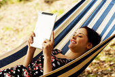 Woman Relaxing In Hammock With  E-Book — Stock Photo