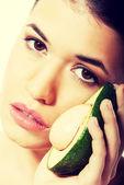 Beautiful woman holding avocado — Stock Photo