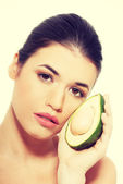 Beautiful womans face with avocado — Stock Photo