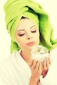 Beautiful woman holding face cream. — Stock Photo