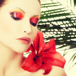 Beautiful woman with a red lily — Stock Photo