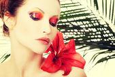 Güzel bir kadın ile kırmızı bir zambak — Stok fotoğraf