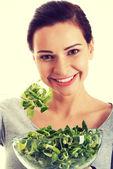 Young casual woman eating lambs lettuce. — Stock Photo