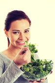 Young casual woman eating lambs lettuce. — Foto de Stock