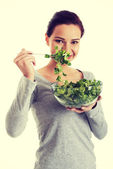 Young casual woman eating lambs lettuce. — Foto Stock