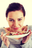 Beautiful young woman with cookies on a plate. — Stock Photo