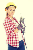 Woman holding drill and wearing safety helmet. — Stock fotografie