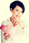 Businesswoman putting a coin into a piggy bank — Stock Photo
