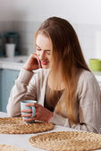 Woman sitting in kitchen — Stock Photo