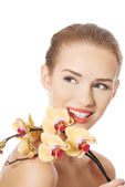 Portrait of beautiful woman with orchid flower. — Stock Photo