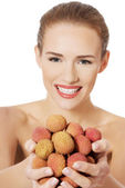 Woman holding handful of lychees — Stock Photo