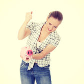 Woman trying to get money from her piggy bank — Stock Photo