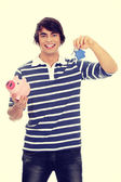 Young man with key and piggybank. — Stock Photo