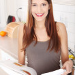 Young woman reading cookbook in the kitchen — Stock Photo #5064938