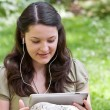 Young woman with tablet PC in a garden — Stock Photo