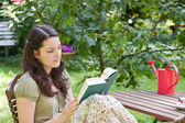 Young woman is reading in a garden — 图库照片