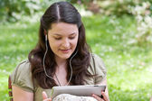 Young woman with tablet PC in a garden — 图库照片