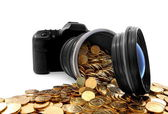 Slr camera with lens full of golden coins — Stock Photo
